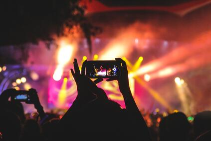 A person holding a phone at a music concert
